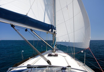 Sailing yacht on back wind on blue sea and blue sky