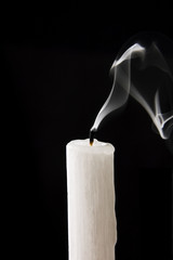 Extinguished candle with smoke over black background