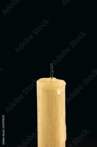 Extinguished candle with tear of wax over black background