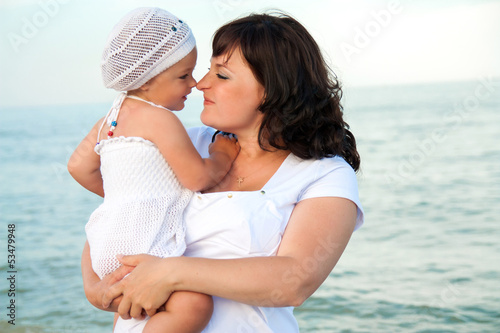 Young pregnant woman with her daughter on the beach.