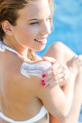 woman in white bikini applying sunblock at the pool