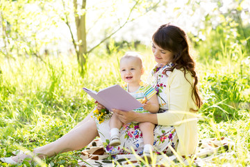 happy mother reading a book to baby outdoors