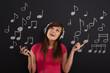 Happy woman listening to music through headphones