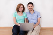 Portrait of young happy couple sitting on floor using laptop