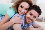 Happy Young Couple Lying On Front