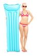 Young woman in bikini holding a swimming mattress