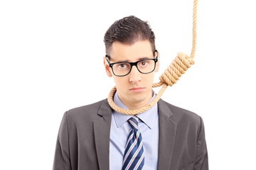 Depressed businessman in suit executing a suicide with a rope