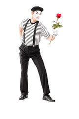 Full length portrait of a mime asrtist giving a rose flower
