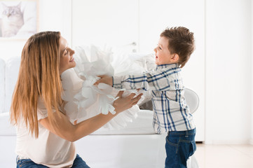 Joyful toddler playing with paper home decoration and his mother