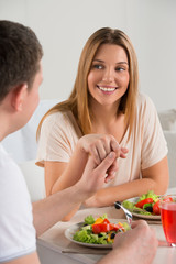 Young happy couple eating vegetable salad