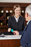 Receptionist in hotel greeting senior man