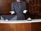 Concierge behind hotel reception counter