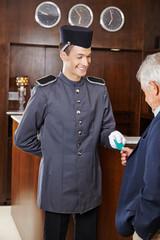 Concierge giving senior man hotel key card