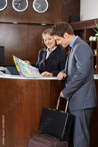 Guest looking at city map with hotel receptionist