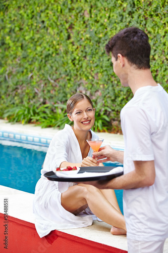 Woman taking cocktail from waiter at hotel pool