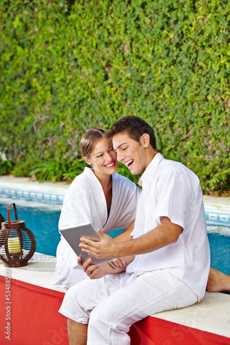 Couple at pool with tablet PC