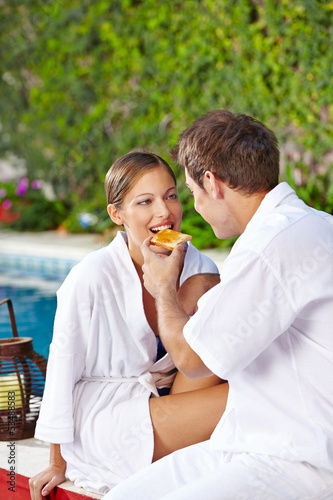 Couple having breakfast at pool