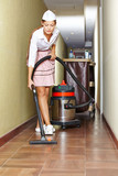 Cleaning lady with vacuum cleaner in hotel
