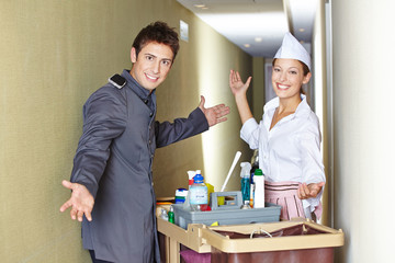 Concierge and hotel maid with cleaning cart