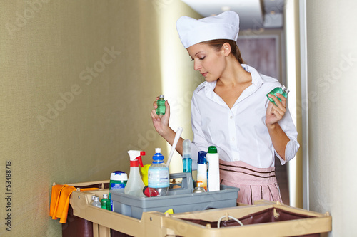 Hotel maid with cleaning cart and cleaning supplies