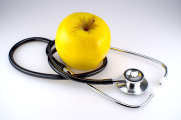 A stethoscope with a yellow apple
