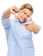 Happy young man framing photograph using fingers isolated on whi