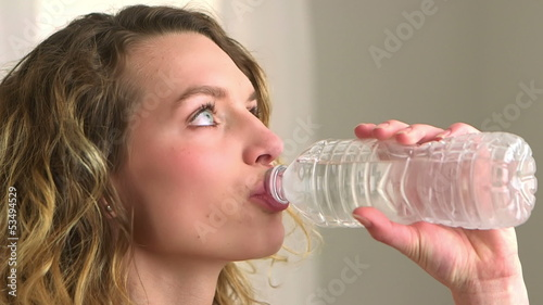 Close-up of blonde woman drinking bottled water