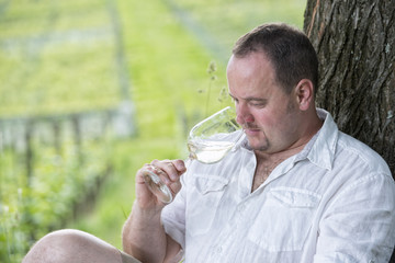 Winemaker drinks white wine