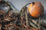 Old tangled fishing nets with orange sphere buoy
