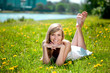 Beautiful smiling woman lying on the grass