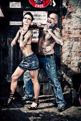 Couple with tattoos at junkyard