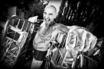Man with tattoos at junkyard