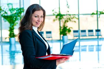 Happy businesswoman holding an open folders