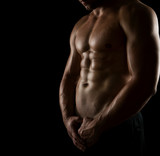 Close up of perfect male body isolated on black