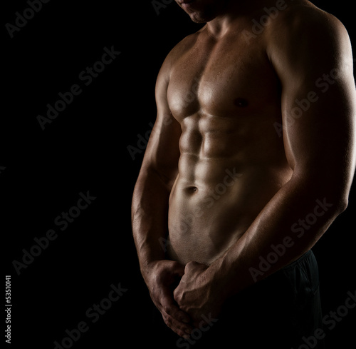Close up of perfect male body isolated on black - 53510141