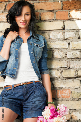 Beautiful young woman at the brick wall