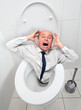 Frightened businessman screaming from toilet bowl.