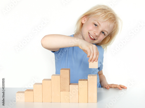 Little girl is building with bricks