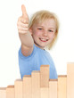 Girl shows thumb up for bulding with bricks