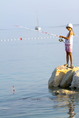 Fishing - lovely girl fishing in the sea