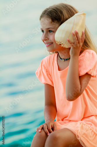 Summer relax - lovely girl with shell on the beach