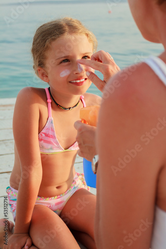 Sun protection - Mother anoints her daughter face sunblocker