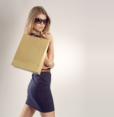 Glamour blonde lady in sunglasses with a shopping bag.