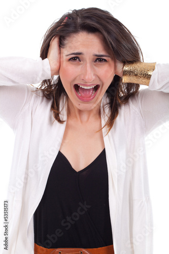Portrait of a unhappy young woman covering her ears and screamin