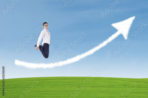 Businessman jumping over success arrow sign cloud