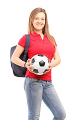 Young smiling female student holding a soccer ball