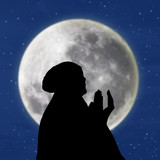 Silhouette of female muslim on blue moon