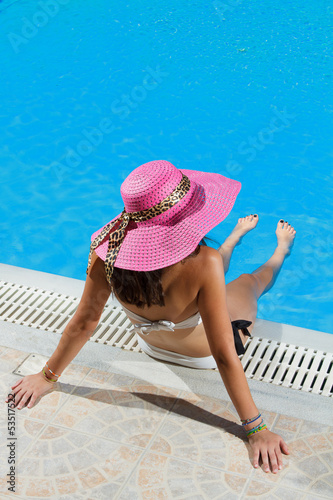 Woman sitting on the ledge of the pool.