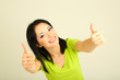 Happy young woman showing thumbs up sign on grey background