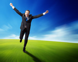 happy business man running on blured spring field